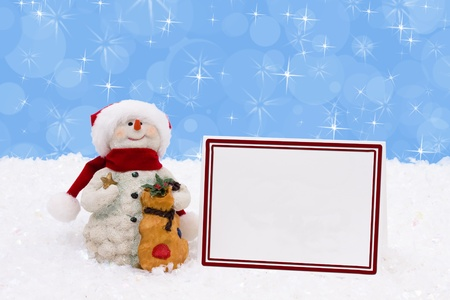 A snowman with a blank card on a snow background, Winter time photo