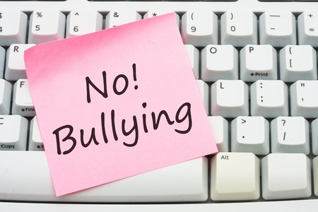 A computer keyboard with a sticky note saying no bulling, Stop internet bullying photo