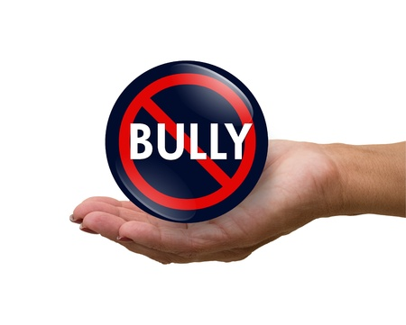 A blue, white and red  button with word Bully isolated on a white background in a hand, No Bully button Stock Photo - 12082537