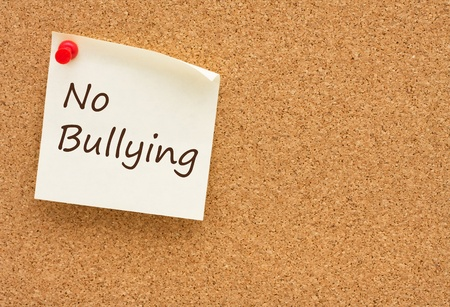 A yellow sticky note on a cork board with the words no bullying on it Stock Photo - 12358613