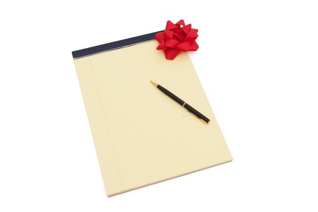 Blank yellow lined notepad with copy-space, red bow List and a pen, Making your Wish List