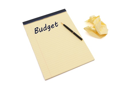 rewrite: Blank yellow lined notepad with copy-space, a pen, and crumpled paper, Writing your Budget