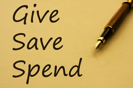 A fountain pen with yellow paper and words give, save and spend, Where your money is spent
