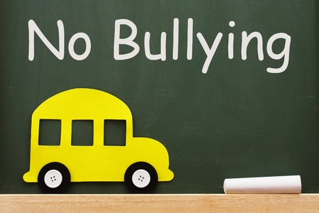 A school bus and chalk on a chalkboard with words no bullying, No bullying allowed photo