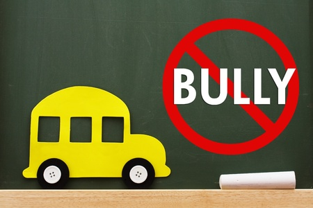 A school bus and chalk on a chalkboard with no bully sign, No bullying allowed photo