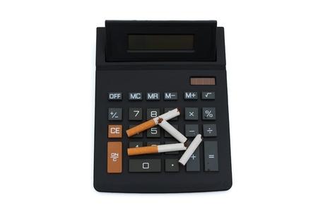 cease: Una calcolatrice con alcune sigarette spezzate isolati su bianco, calcolando il costo del fumo