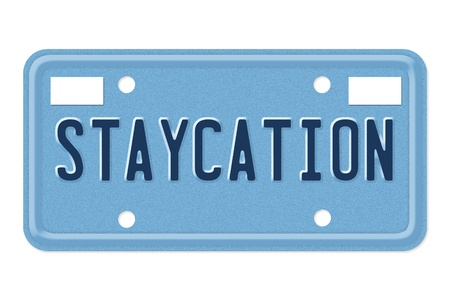 staycation: A blue license plate with the word staycation isolated over white