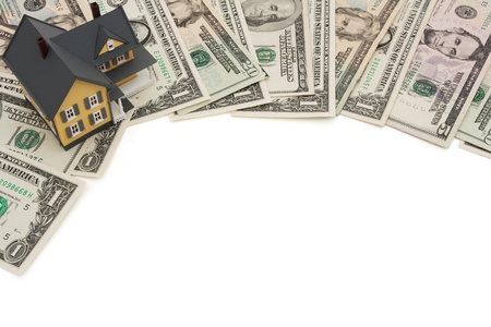 A border of American money with a yellow house isolated on white, The cost of  housing photo