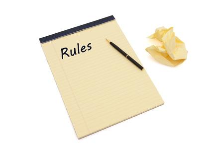 regel: Blank geel bekleed kladblok met exemplaar-ruimte, een pen, en proppen papier, definiëren van uw regels