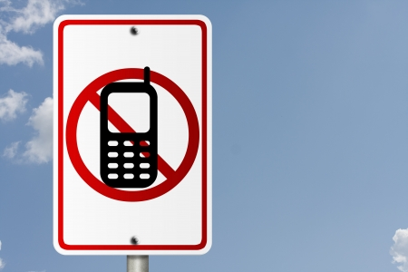 sms: An American road sign with sky background and copy space for your message, No Cell Phones while driving