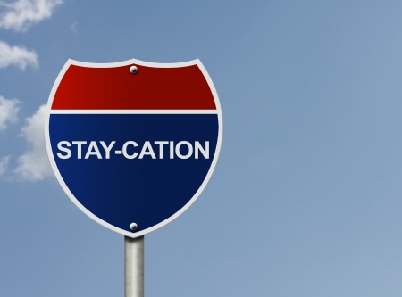 staycation: An American interstate road sign with words Stay-cation over a sky background, Taking a stay-cation Stock Photo