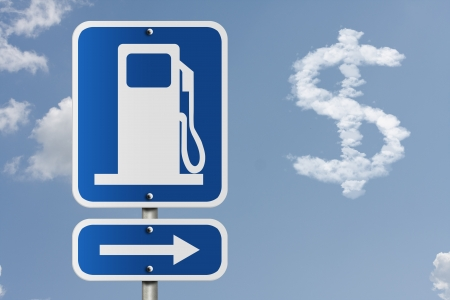 An American road sign with gas symbol, arrow, and dollar sign in the clouds, The price of gas photo