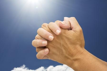 manos orando: Mujeres manos rezando con un fondo del cielo, orando las manos Foto de archivo