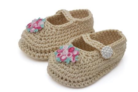 ecru: Ecru crochet baby booties with flowers isolated on white, Hand-made baby booties Stock Photo