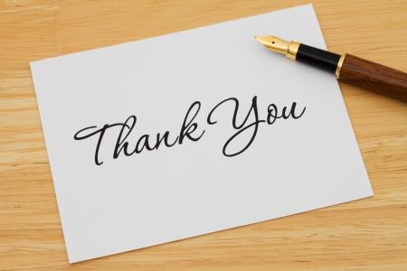 Ein Dankeschön-Karte mit einem Füllfederhalter auf einem hölzernen Schreibtisch, Schreiben einen Dankesbrief