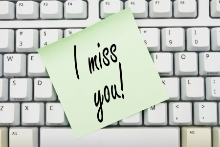 Computer keyboard keys with sticky note with words I miss you, Spending too much time on internet