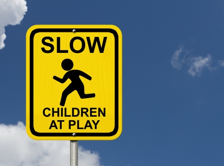 An American road warning sign with sky with child running symbol and words Slow  Children at Play, Beware Children are present photo