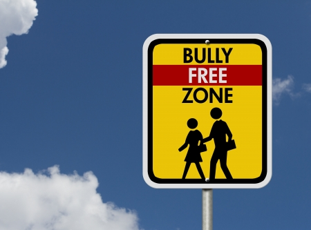 An American road warning sign with sky with children walking symbol and words Bully Free Zone, Caution This is a Bully Free Zone  photo
