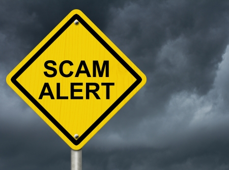 alert: A road warning sign against a stormy sky with words Scam Alert, Warning of Scam