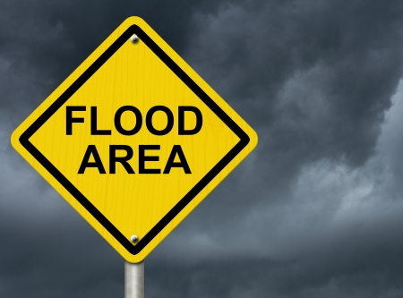 flood area: A road warning sign against a stormy sky with words Flood Area, Flood Warning