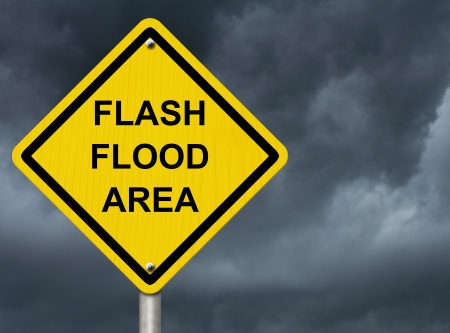 A road warning sign against a stormy sky with words Flash Flood Area, Flood Warning photo