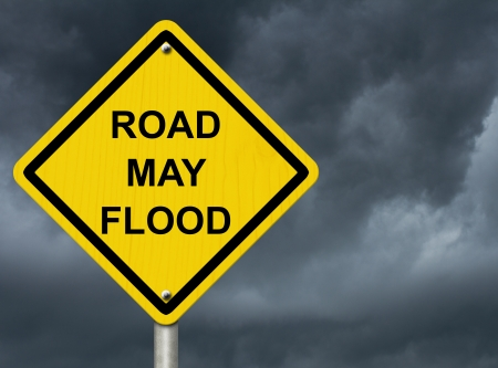A road warning sign against a stormy sky with words Road May Flood, Flood Warning photo