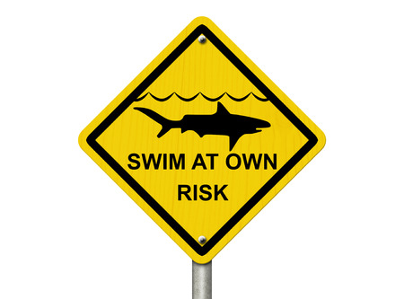 An warning sign isolated on white with shark symbol and words swim at own risk, Use caution when swimming because sharks are present  photo