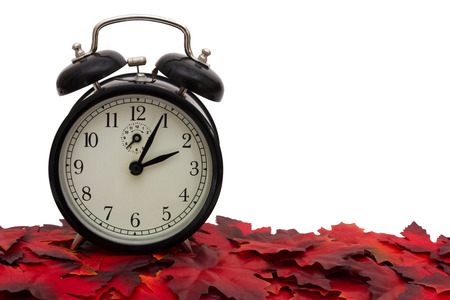clock: Black Alarm Clock on Red Autumn Leaves isolated on white for copy-space, Autumn Time