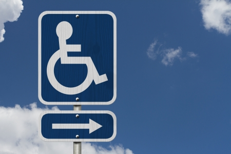 disabled parking sign: An Blue American road sign with a wheelchair and arrow with sky background, HandicapParking Sign
