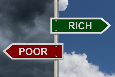 言葉金持ちと貧しい人々 は、貧しい人と豊かな青い嵐の空に赤と緑の道路標識 写真素材