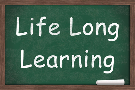 continuing education: Life Long Learning written on a chalkboard with a piece of white chalk