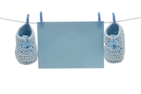 A blue blank card hanging on line with baby booties isolated on a white background for you message photo