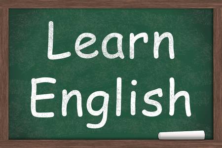 english text: Learning English, Learn English written on a chalkboard with a piece of white chalk