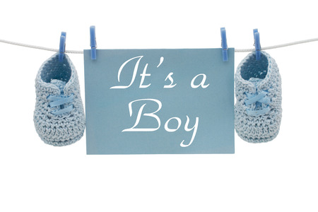 baby boy announcement: A blue card hanging on line with baby booties isolated on a white