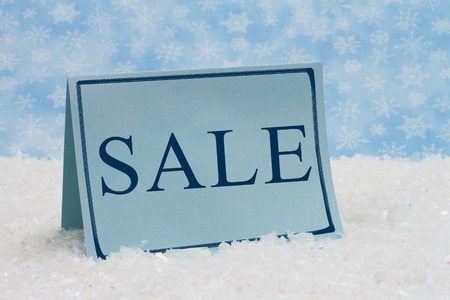 Winter Sale Message,A blue blank card on snow and a blue snowflake background with text of  Sale photo
