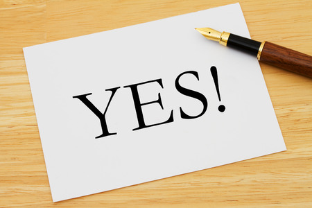A white card with text of yes and a fountain pen on a wooden desk, Saying yes! photo