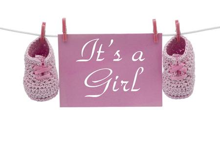 Una tarjeta de color rosa colgando en línea con botines del bebé aislado en un blanco para el mensaje, es un aviso de la muchacha