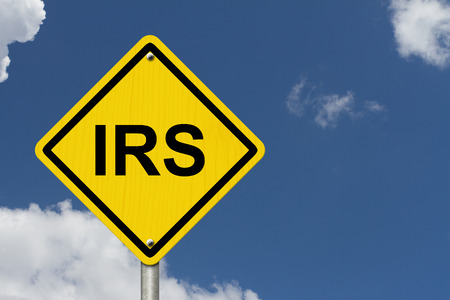 An American road warning sign with word IRS with a sky background photo