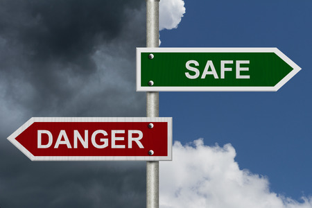 danger: Red and green street signs with blue and stormy sky with words Safe and Danger, Safe versus Danger