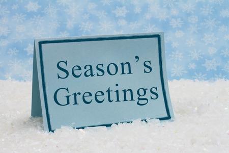 Het Groetenbericht van het seizoen, een blauwe lege kaart op sneeuw en een blauwe sneeuwvlokachtergrond met tekst van de Groeten van het Seizoen