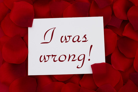 I was wrong card, A white card with text I was wrong and a red rose pedal backgrounds photo