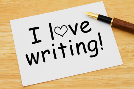 I love writing, A white card with text of I love writing and a fountain pen on a wooden desk Stock fotó
