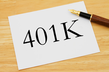401K Planning, A white card with text of  401K and a fountain pen on a wooden desk photo