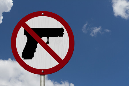 precaution: No Firearms Allowed Sign, An red road sign with handgun icon and not symbol with blue sky