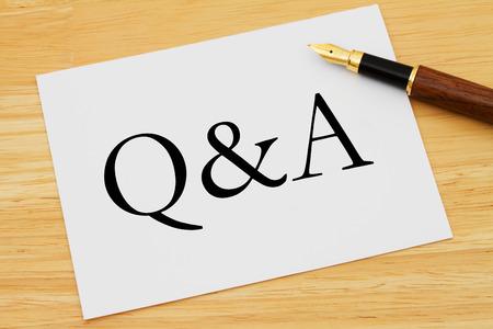control de calidad: Q & A, una tarjeta blanca con el texto de Q & A y una pluma sobre un escritorio de madera
