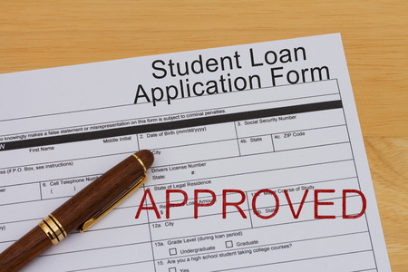 Student Loan Application Form with a pen and approved stamp on a wooden desk