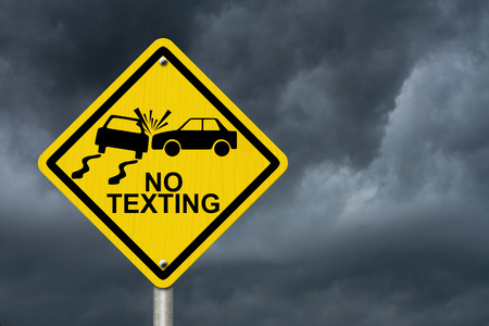 No Texting While Driving Sign, Yellow warning sign with words No Texting and accident icon with stormy sky background photo