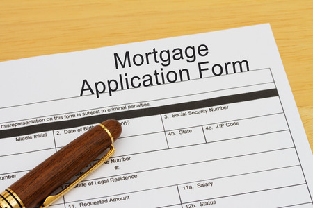 borrowing: Mortgage Application Form with a pen on a wooden desk