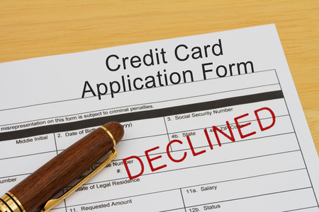 borrowing: Credit Card Application Form with an declined stamp and a pen on a wooden desk Stock Photo