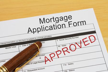tampon approuv�: Formulaire de demande de pr�t hypoth�caire avec le timbre approuv� et un stylo sur un bureau en bois